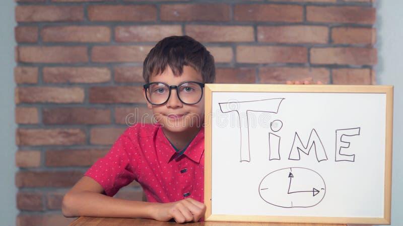 Criança que senta-se na mesa que guarda o flipchart com rotulação do tempo imagem de stock royalty free
