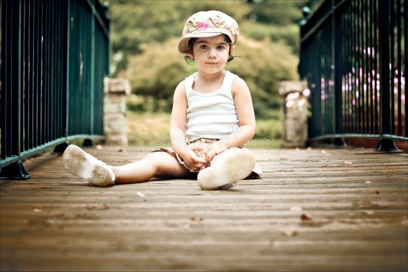 Criança que senta-se na ponte imagens de stock royalty free