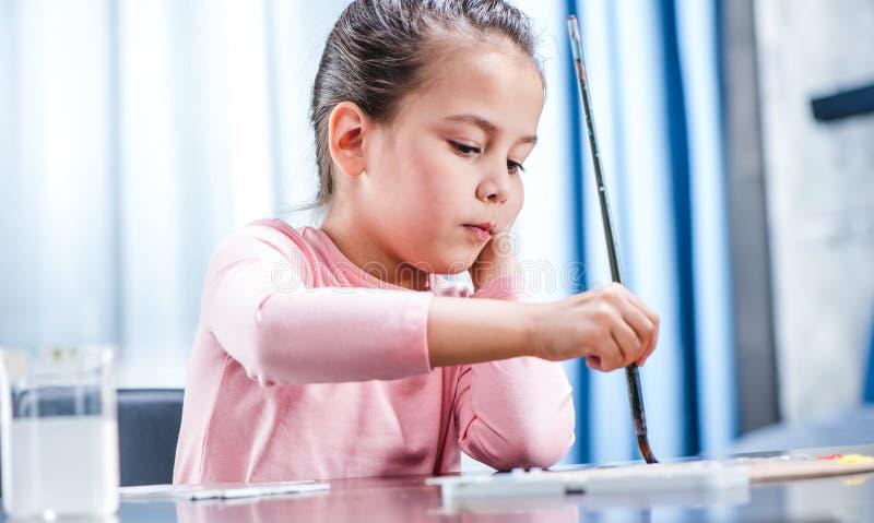 Criança que senta-se na tabela e que pinta animal no papel fotografia de stock