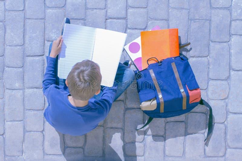Criança que senta-se na terra e que lança através das páginas do caderno imagem de stock