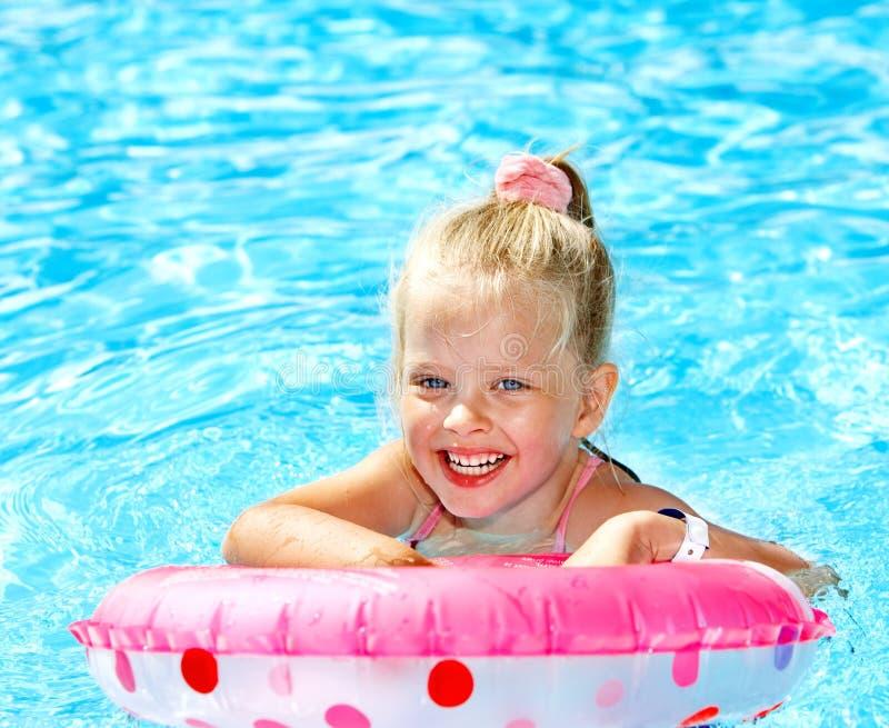 Criança que senta-se no anel inflável na piscina. foto de stock royalty free