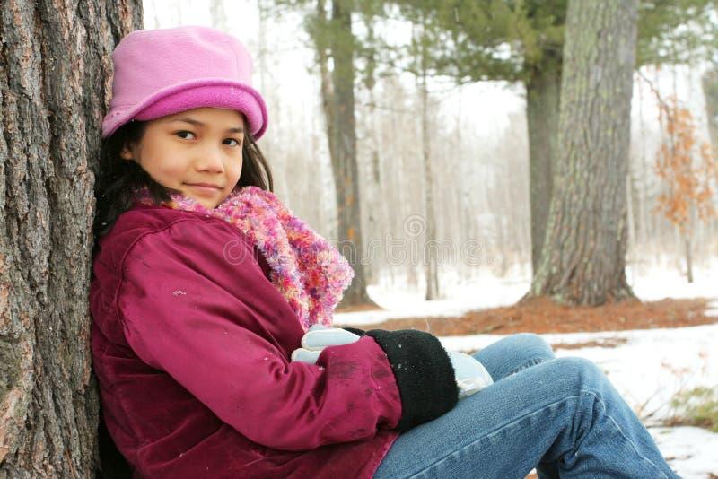 Criança que senta-se sob a árvore ao ar livre no inverno imagem de stock