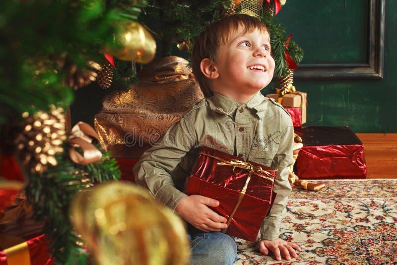 Criança que senta-se sob a árvore de Natal com presentes fotos de stock