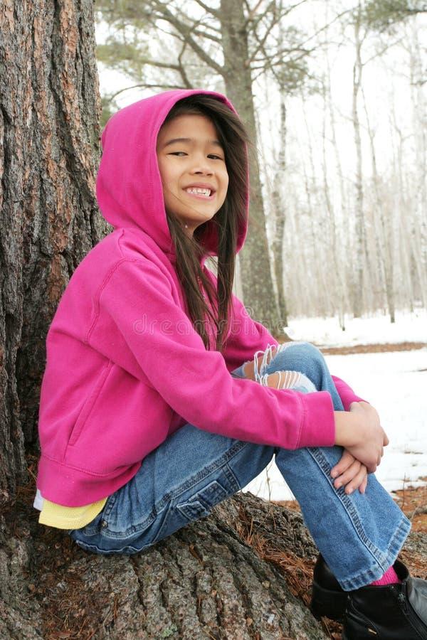 Criança que senta-se sob a árvore no inverno fotos de stock royalty free