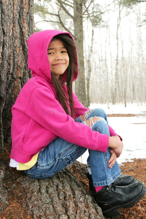 Criança que senta-se sob a árvore no inverno foto de stock royalty free