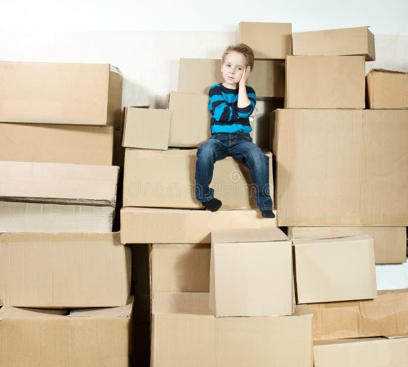 Criança que senta-se sobre caixas da caixa do montão. imagem de stock