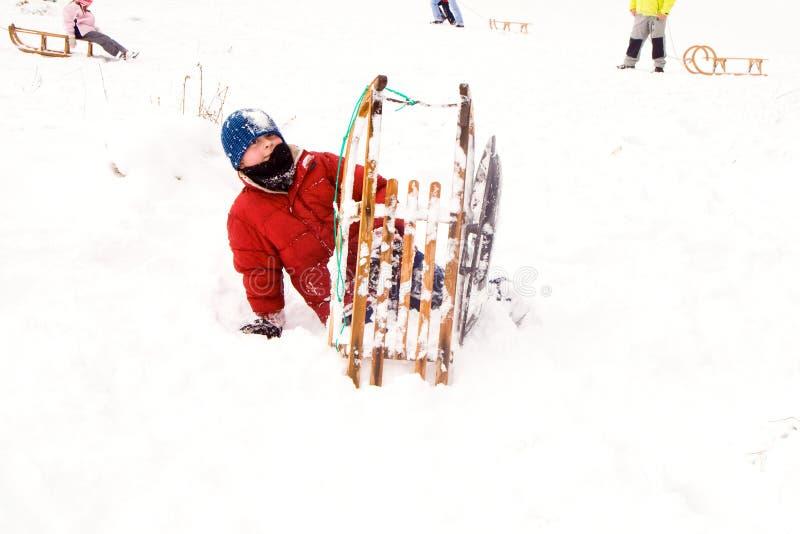 Criança que sledding abaixo do monte na neve, inverno branco foto de stock royalty free