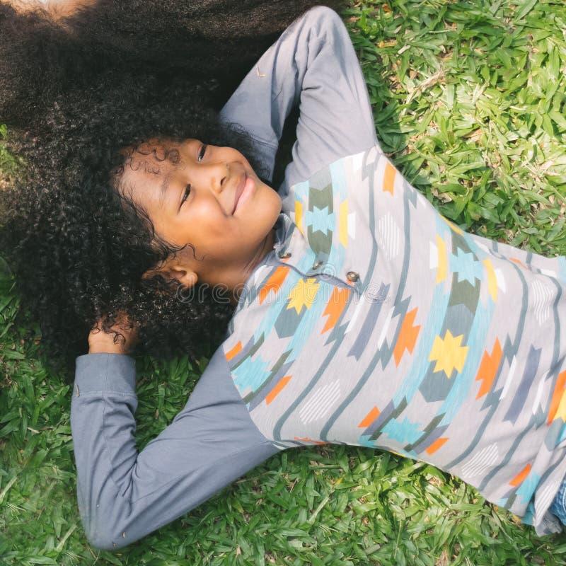 Criança que sorri e que coloca na grama no parque fotografia de stock royalty free