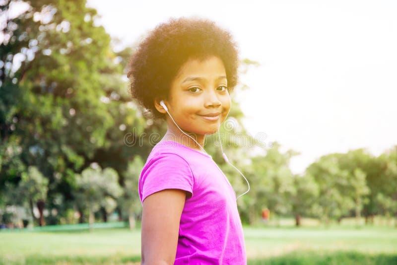 Criança que sorri e que escuta a música no parque verde fotos de stock