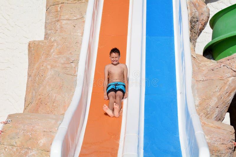 Criança que tem o divertimento em uma corrediça de água imagem de stock