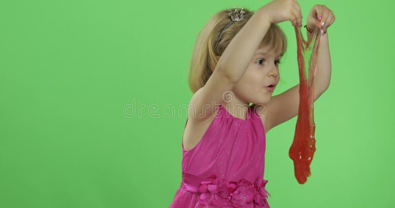 Criança que tem o divertimento que faz o limo vermelho r fotografia de stock