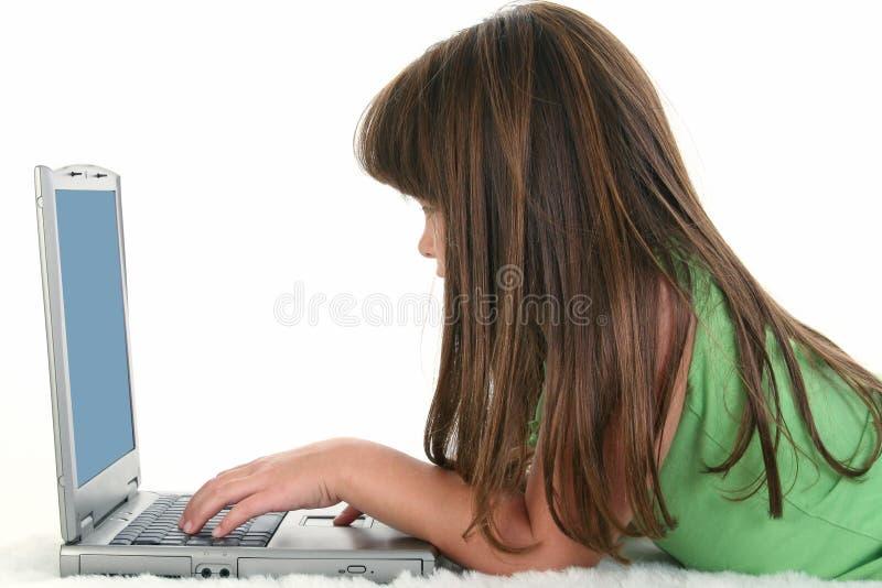 Criança que trabalha no computador portátil