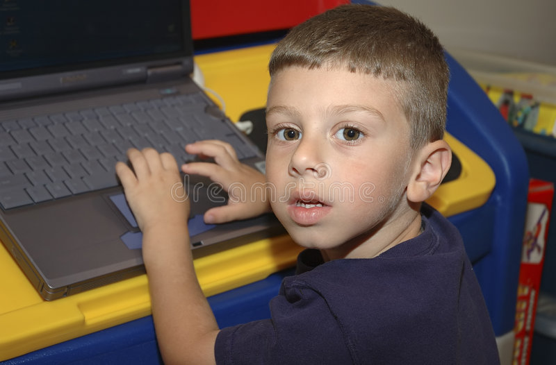 Criança que usa o computador foto de stock