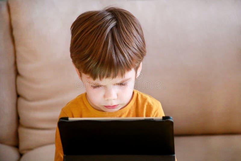 Criança que usa o PC da tabuleta na cama em casa O menino bonito no sofá está olhando desenhos animados, está jogando jogos e est imagens de stock royalty free