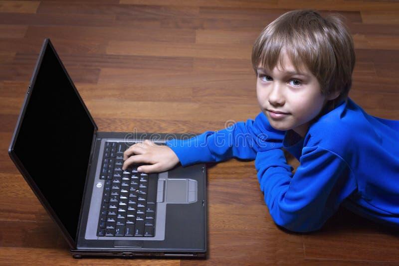 Criança que usa o PC do portátil que encontra-se no assoalho de madeira Vista superior Educação, aprendendo, conceito da tecnolog imagem de stock