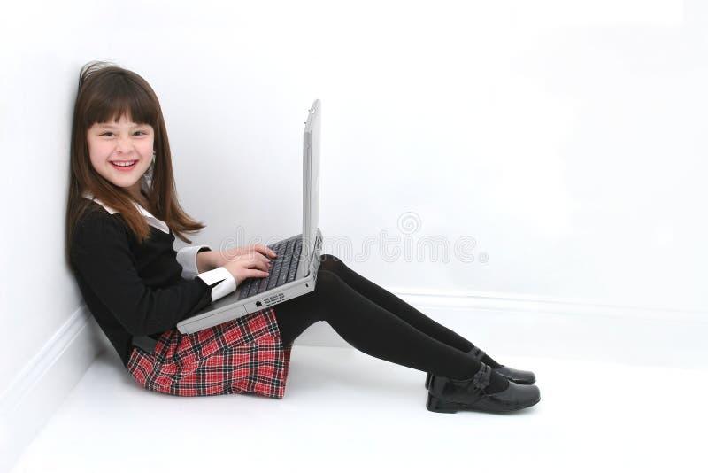 Criança que usa o portátil imagem de stock