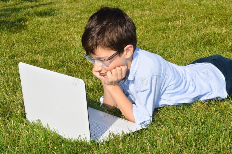 Criança que usa o portátil imagens de stock