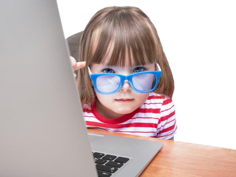 Criança que usa o portátil no fundo branco imagem de stock