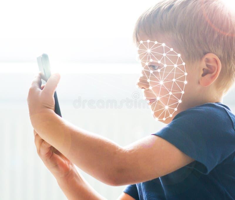 Criança que usa o reconhecimento da identificação da cara Menino com um dispositivo do smartphone Conceito nativo das crianças de imagens de stock