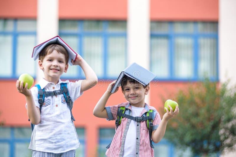 Criança que vai à escola Menino e seu amigo que guardam livros na cabeça fotografia de stock royalty free