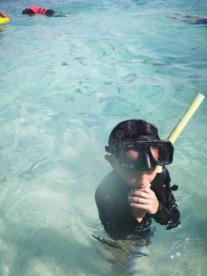Criança que veste mergulhando a máscara na água fotos de stock