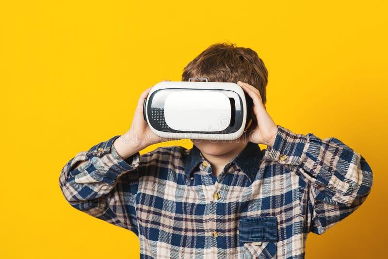 Criança que veste os vidros da realidade virtual, isolados no amarelo Tecnologia futura Menino que usa uns auriculares da realida fotografia de stock royalty free