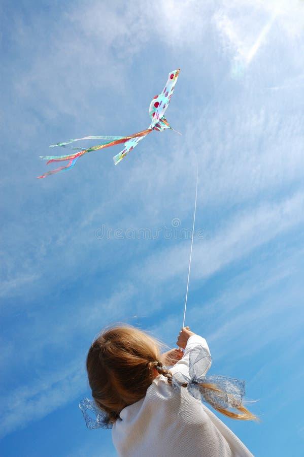 Criança que voa um papagaio fotografia de stock royalty free