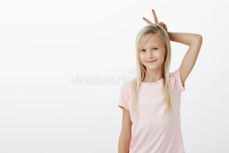 A criança quer jogar com irmão mais velho Retrato da moça adorável bonito com cabelo louro, guardando a vitória ou a paz foto de stock royalty free
