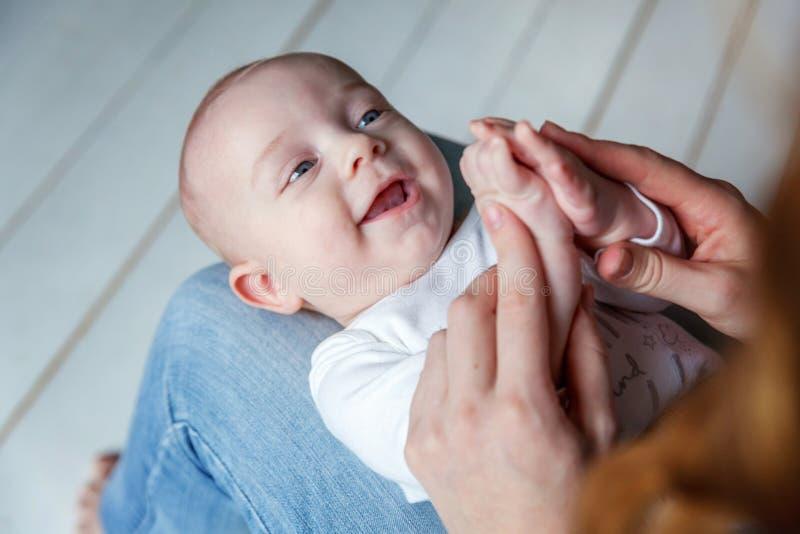A criança recém-nascida encontra-se em seu regaço do ` s da mãe fotos de stock