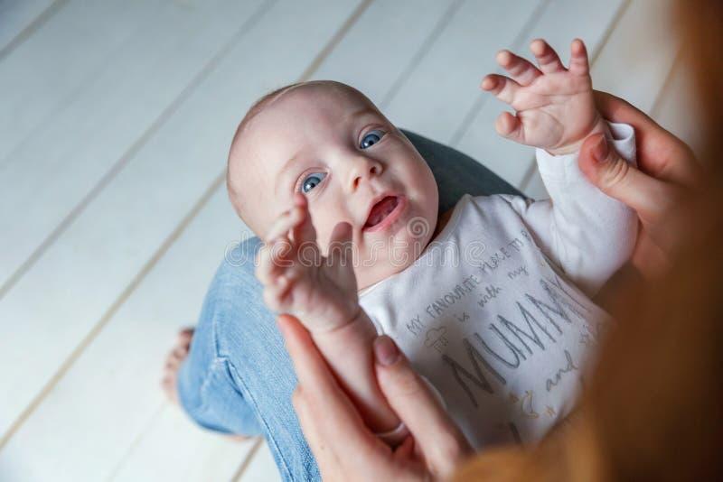 A criança recém-nascida encontra-se em seu regaço do ` s da mãe fotografia de stock