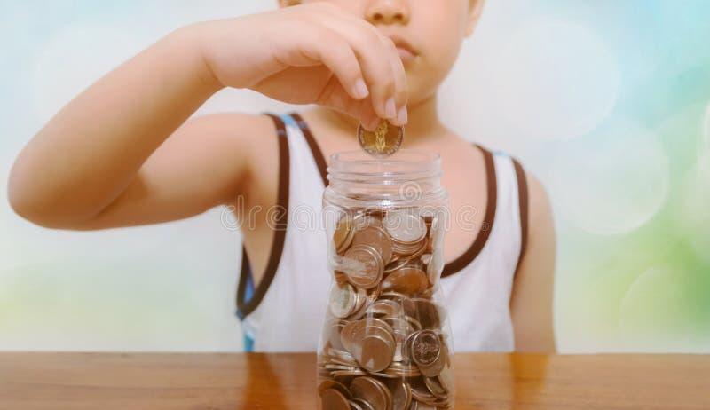 A criança recolhe o dinheiro de salvamento para o futuro fotografia de stock royalty free