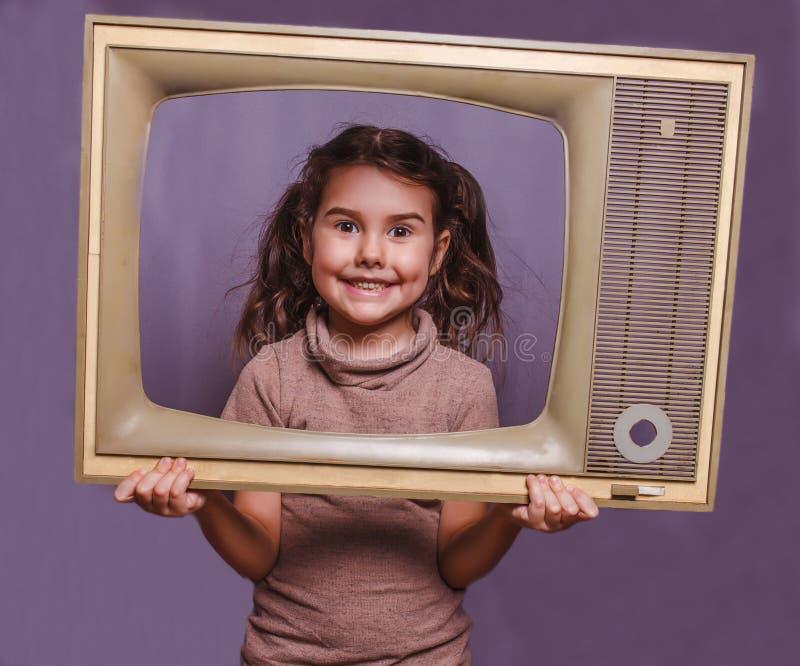 A criança retro da menina adolescente moldou o quadro da televisão que sorri em vagabundos cinzentos fotos de stock