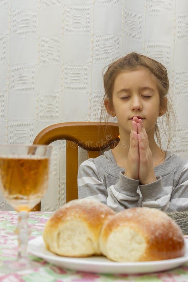 A criança reza em Shabbat Pouco Sabat judaico Criança judaica na tabela do Sabat Foto vertical fotos de stock royalty free
