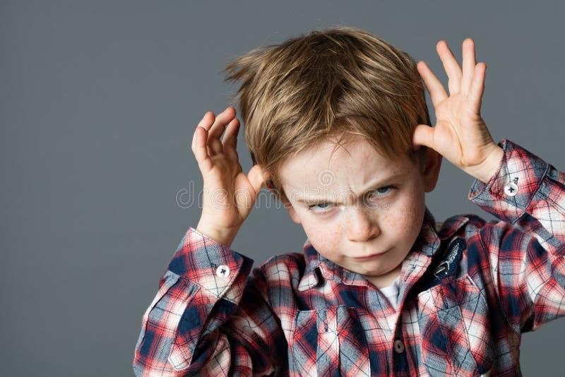 Criança rude que joga com as mãos que fazem a cara para atitude determinada foto de stock royalty free