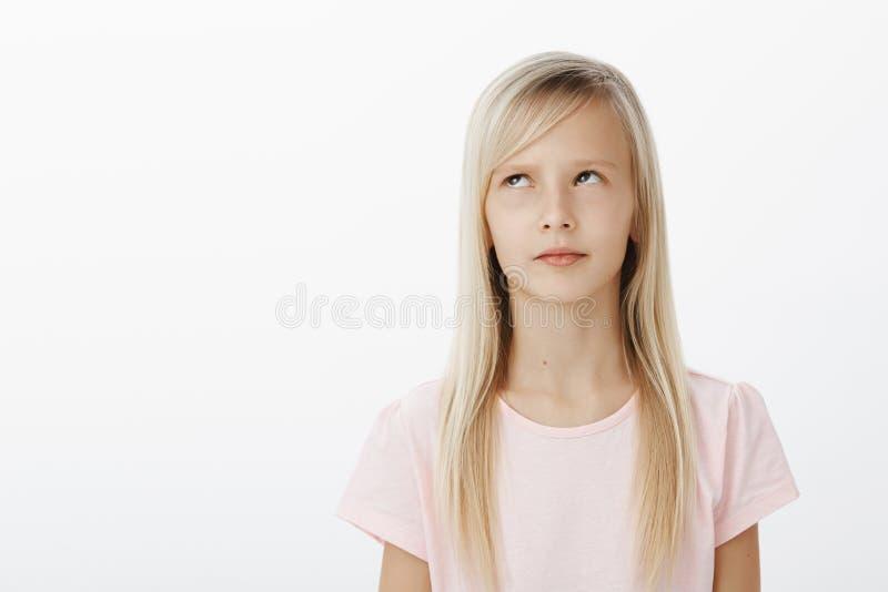 Criança séria focalizada que recorda material instruído ao responder perto do quadro-negro na escola Tiro do estúdio de interessa fotografia de stock