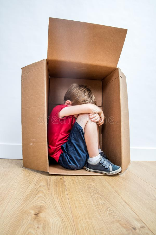 Criança só que grita na caixa, sentindo triste, rejeitado ou assustado imagem de stock