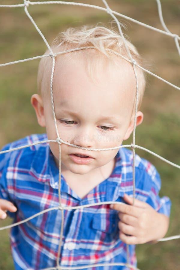 Criança só que joga em uma rede do futebol fotos de stock royalty free
