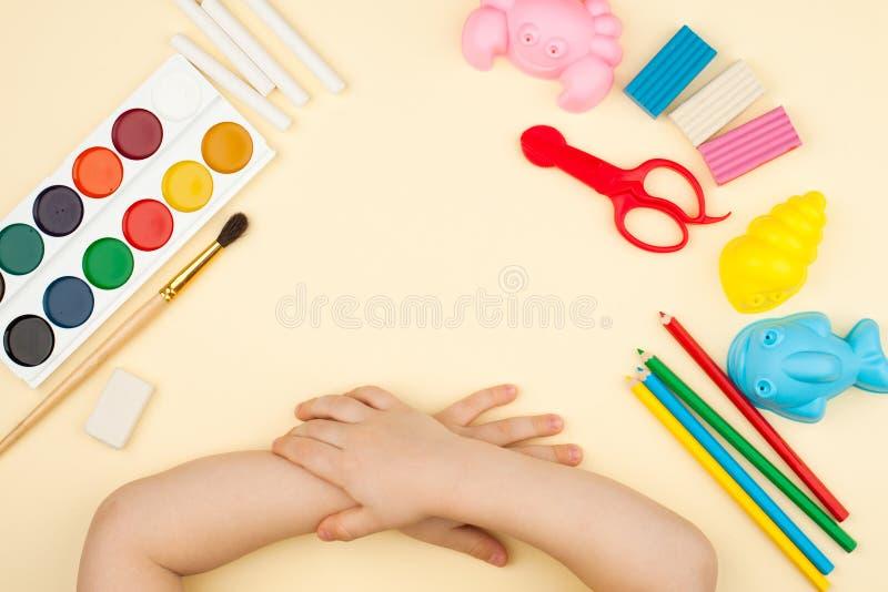 A criança senta-se na tabela com objetos para a faculdade criadora, o desenho e os passatempos, a vista superior fotos de stock
