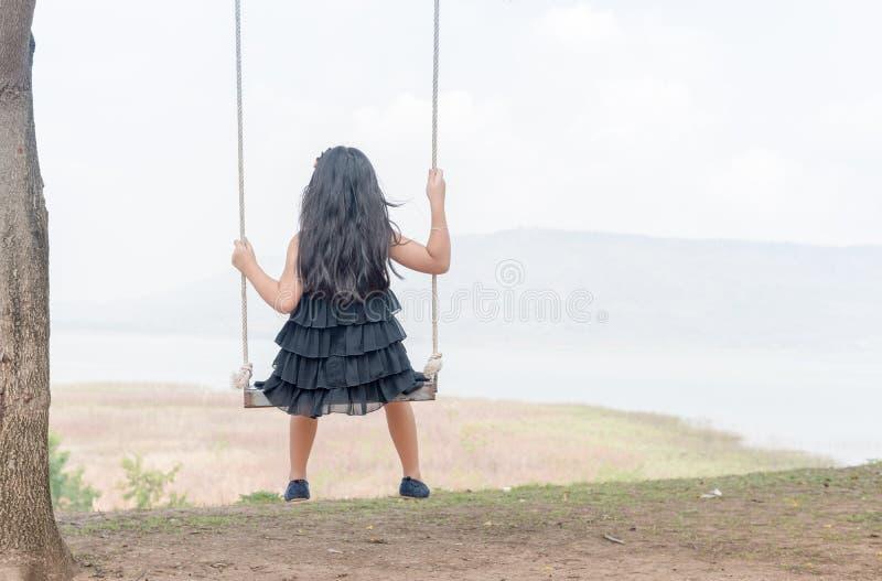 A criança senta-se no assento do balanço no fundo da natureza fotos de stock royalty free
