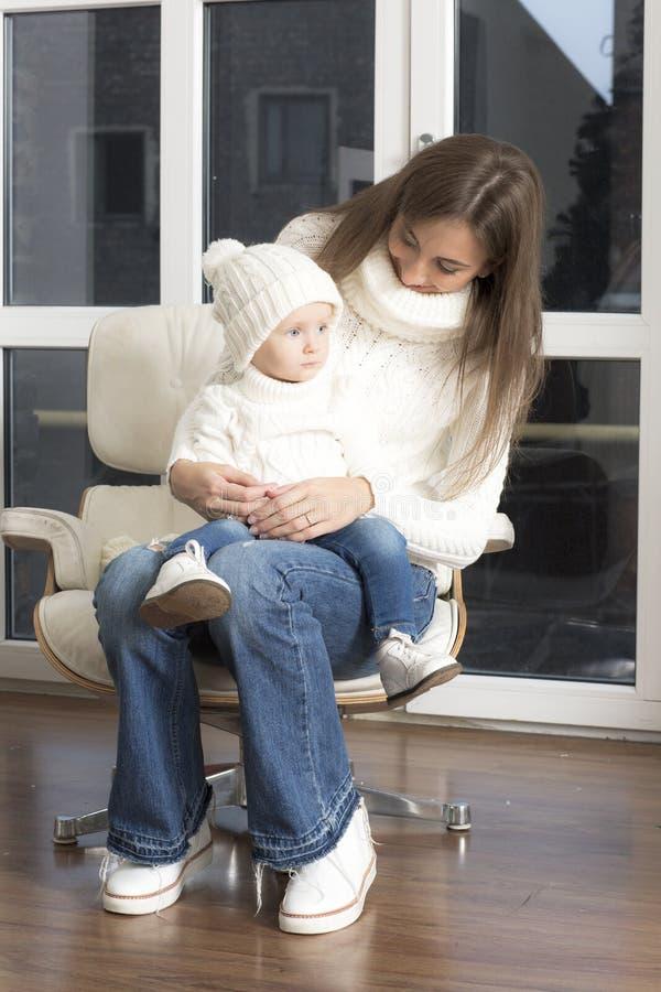 A criança senta-se no regaço da mãe foto de stock royalty free