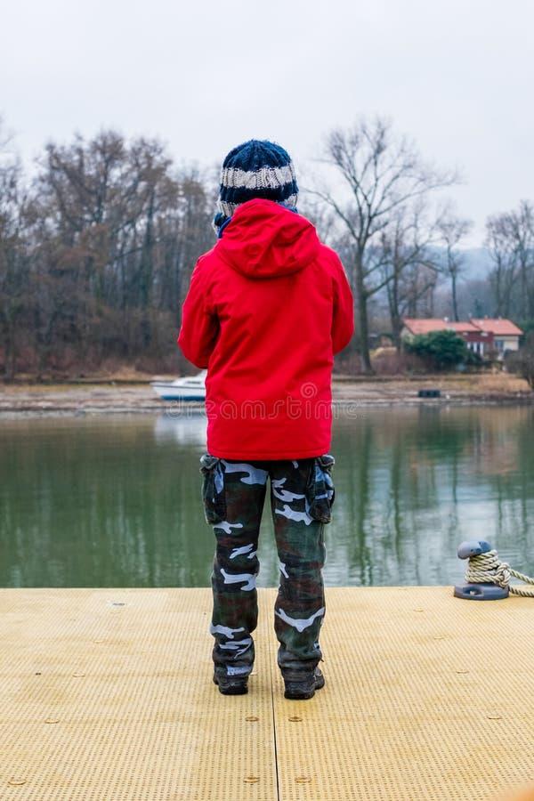 Criança sobre um molhe de madeira no lago Maggiore, névoa do inverno no la fotos de stock