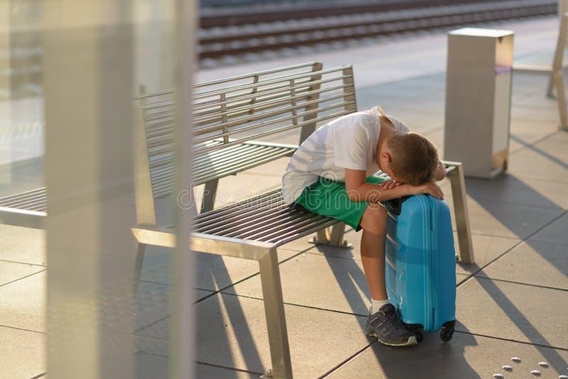 Criança sozinha triste do menino que espera apenas com sua bagagem foto de stock