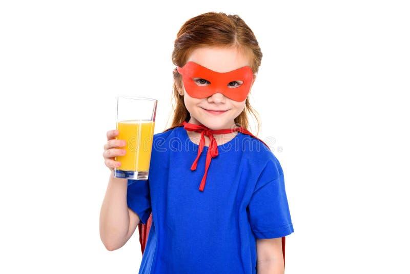 criança super adorável que guarda o vidro do suco e que sorri na câmera imagens de stock