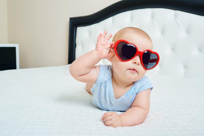 Criança super fresca Bebê engraçado em vidros solares do coração vermelho fotos de stock royalty free