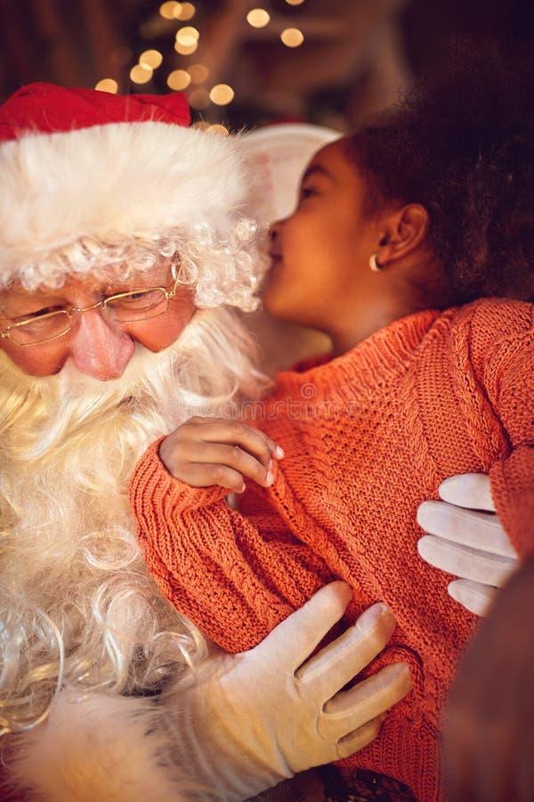 A criança sussurra algo a Papai Noel fotos de stock