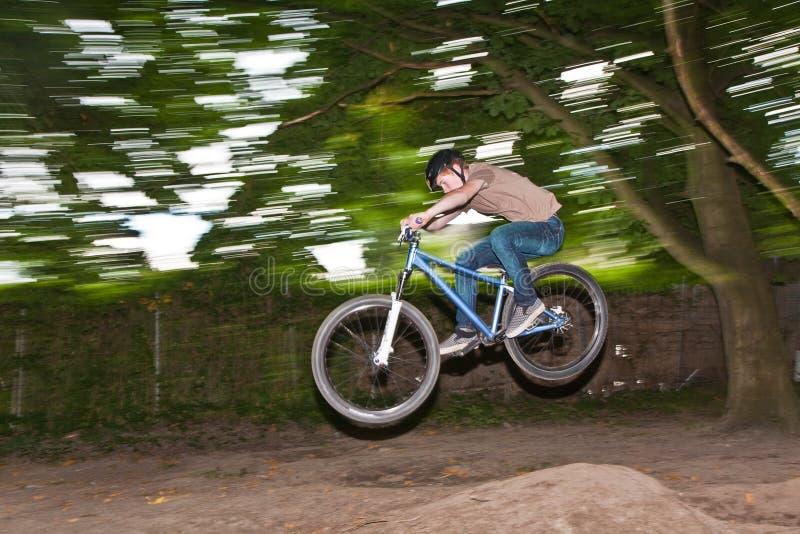A criança tem o divertimento que salta com a bicicleta sobre uma rampa fotos de stock royalty free