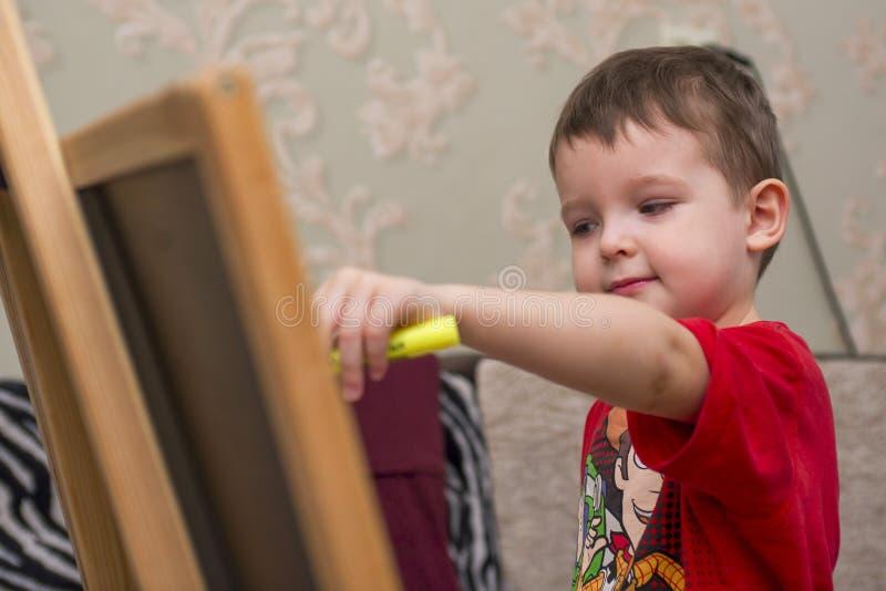 A criança tira em um quadro-negro fotos de stock
