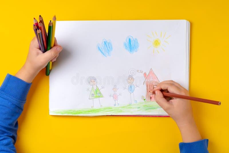 A criança tira sua família em um pedaço de papel com lápis coloridos Minha família feliz O conceito da psicologia de criança fotografia de stock royalty free
