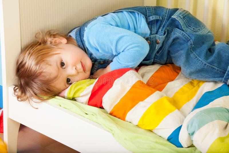 Criança Tired que coloca em sua cama foto de stock royalty free