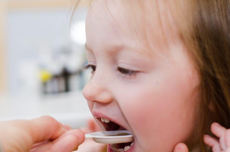 A criança toma a medicina de uma colher foto de stock